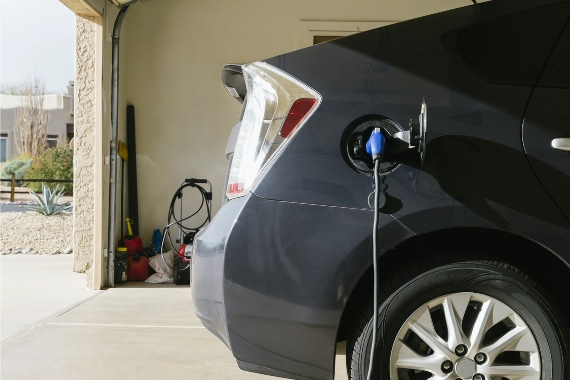 electric car plugged in and charging in garage