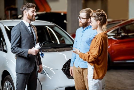 couple at electric vehicle dealership talking to salesman