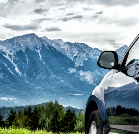 car parked in front of mountain scene