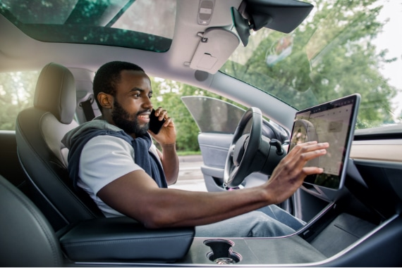 man in electric car using touchpad while on cellphone