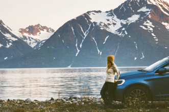 woman with car in front of a fjord and snow topped mountain